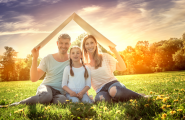Kleinfamilie sitzt auf einer Wiese und hält sich ein Dach über den Kopf.