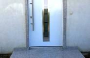 weisse Haustür mit Steinpodest und Stein Rahmen in Kombination durch F.K. Steindesign